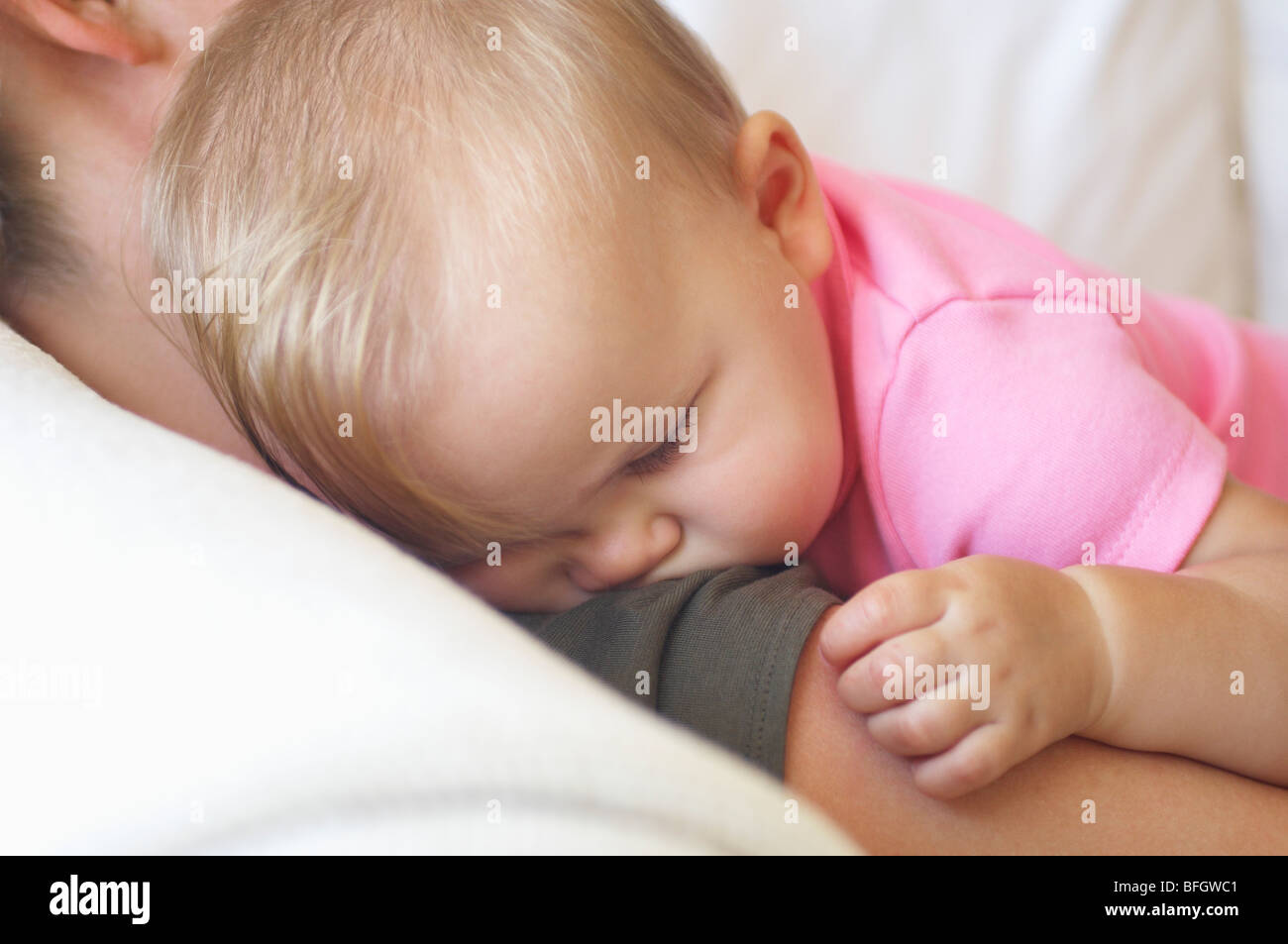 Baby sleeping on mother's shoulder, close up - Stock Image