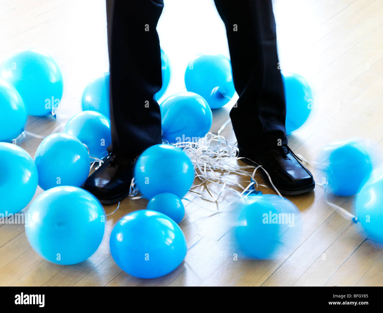 businessman's legs entangled with deflated balloons - Stock Image