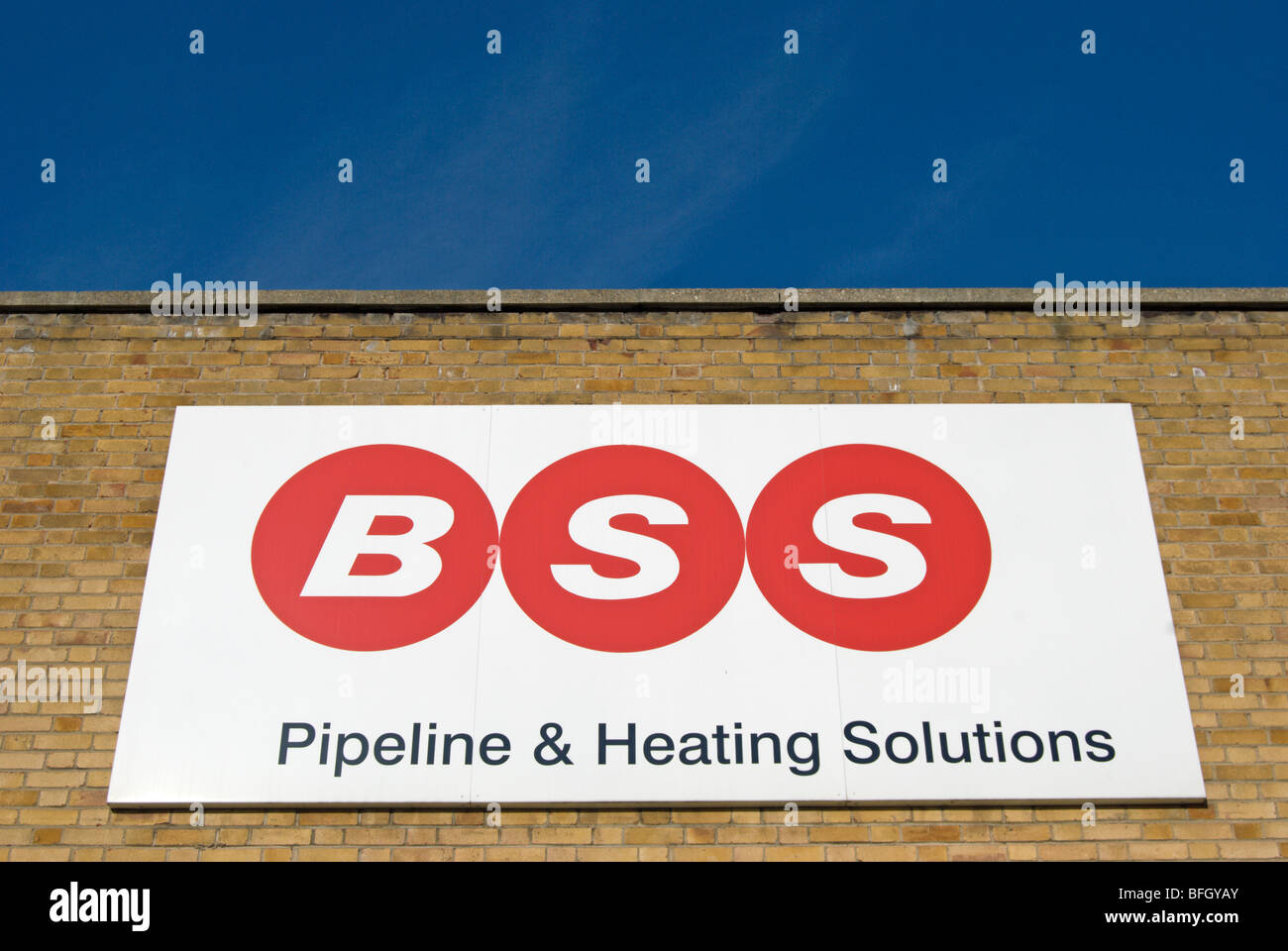 sign with logo for bss pipeline and heating solutions on a brick wall on the great west road, brentford, london, - Stock Image