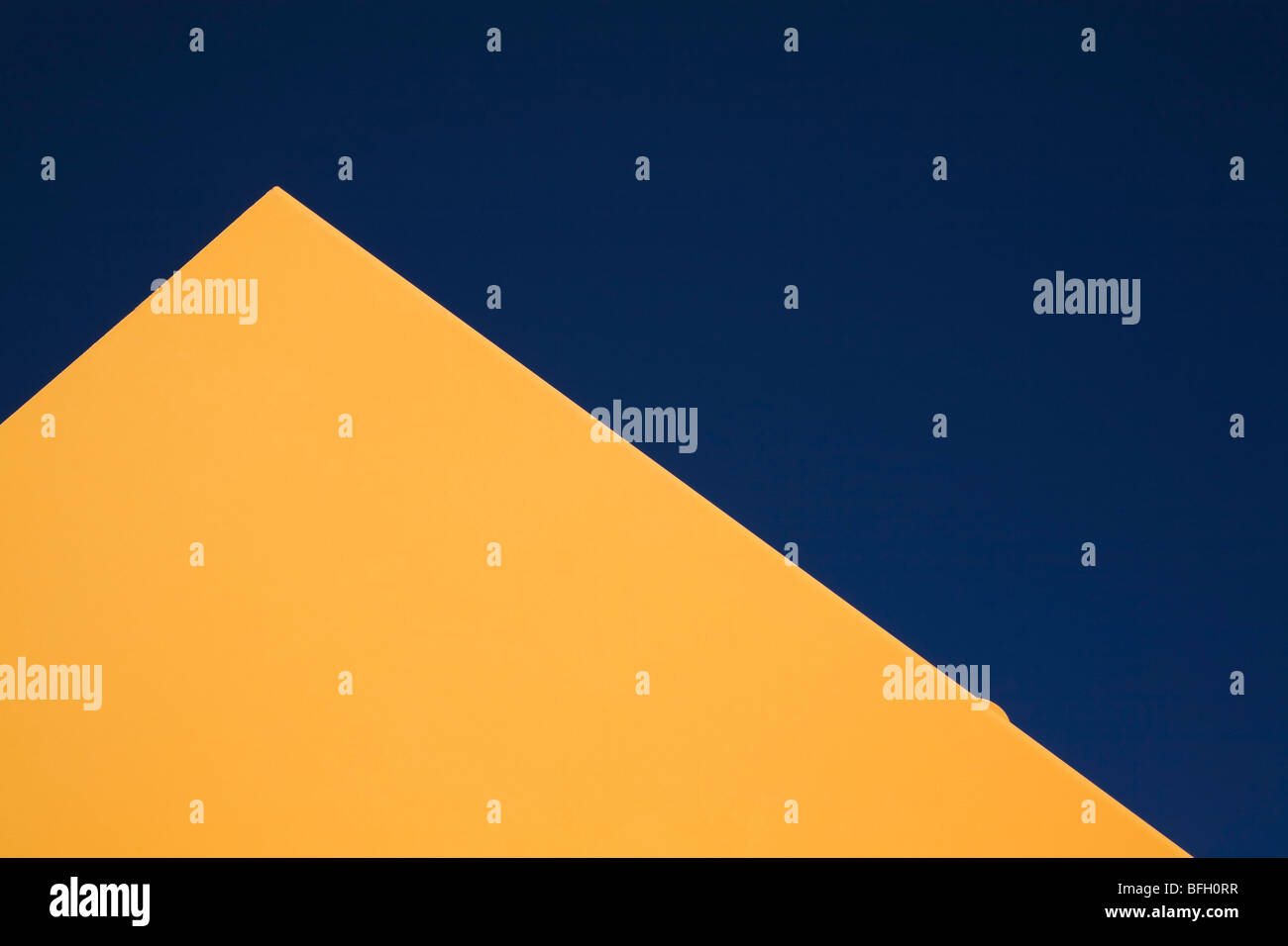 Partial view of a yellow metal shaped pyramid, against a blue sky. Laval, Quebec, Canada - Stock Image