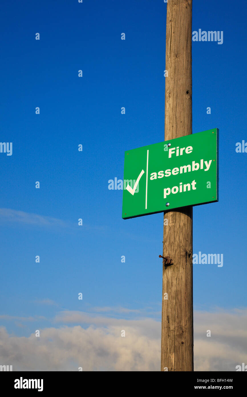 'Fire Assembly' sign on a wooden post against a blue, cloudy sky - Stock Image