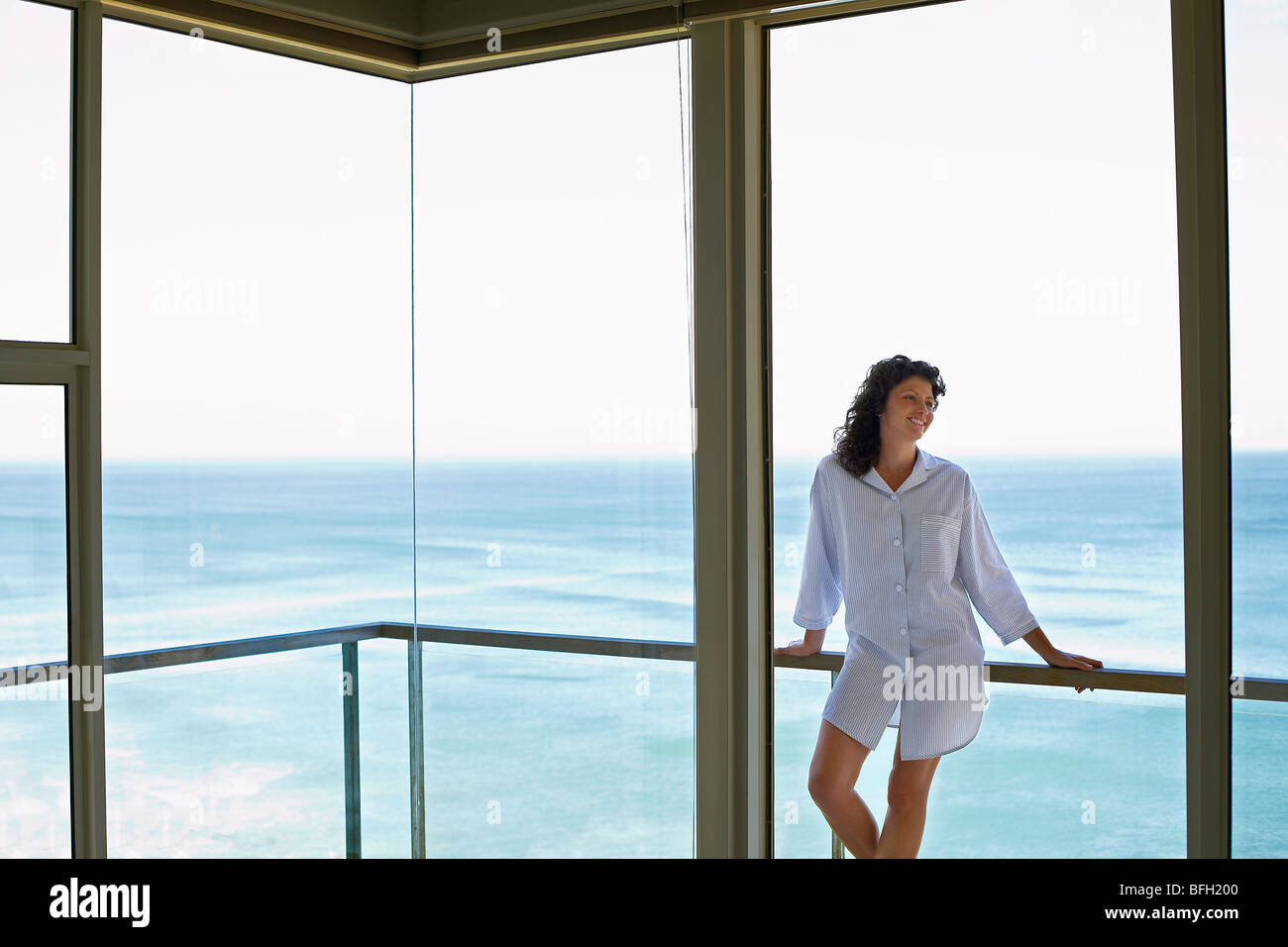 Woman standing on balcony, smiling - Stock Image
