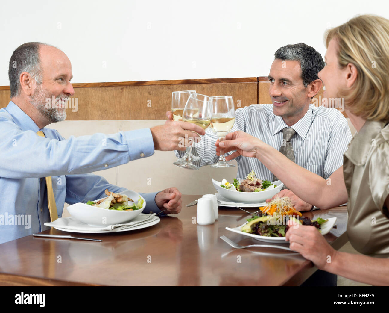 Businesspeople toasting drinks in restaurant - Stock Image