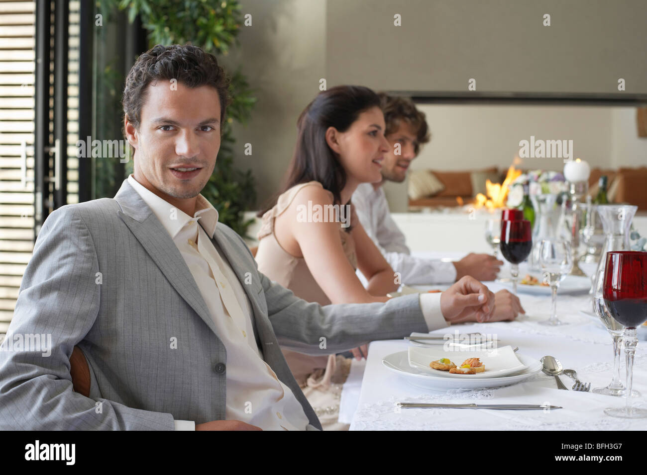 Young, stylishly dressed man sitting at table of formal dinner party, smiling Stock Photo