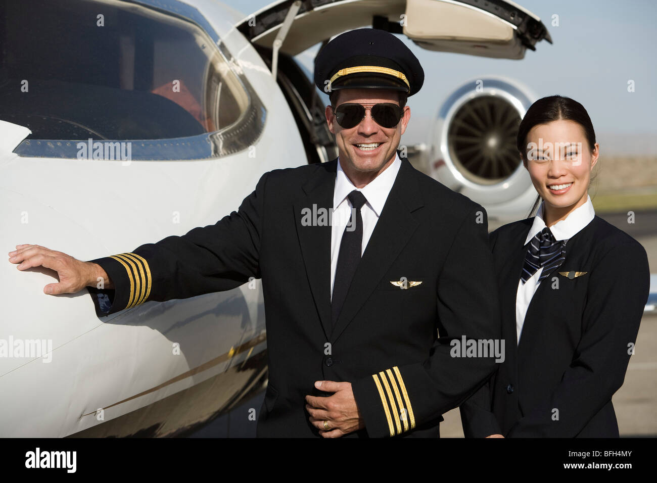 Portrait of mid-adult airline pilot and flight attendant in