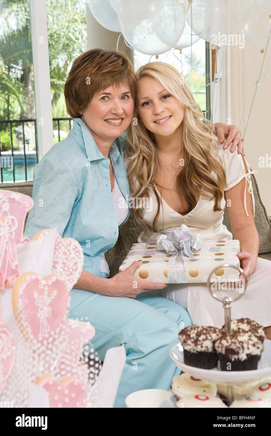 bride and her friend sitting together holding gift at bridal shower