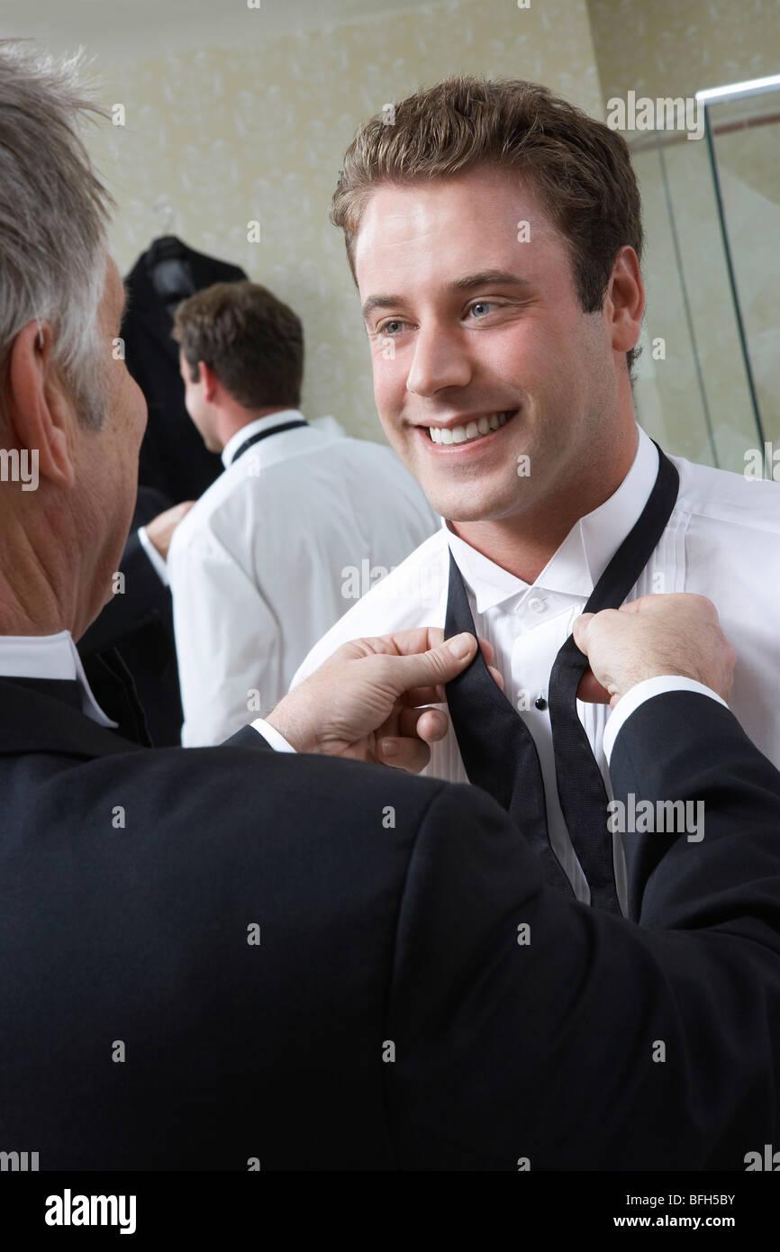 Man tying groom's bow tie - Stock Image