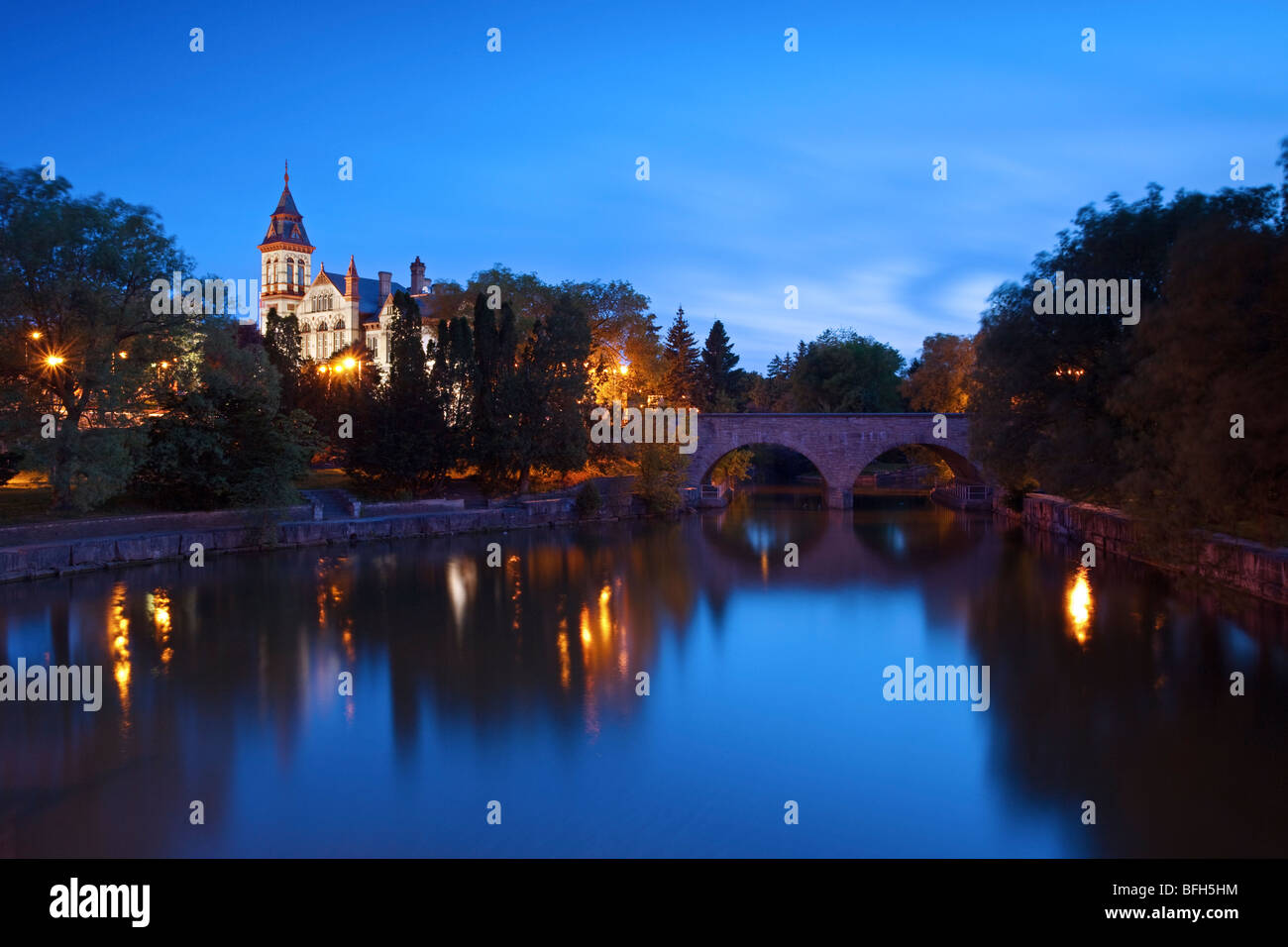 A night view of the Stratford courthouse in Stratford Ontario with the Avon river in the foreground - Stock Image