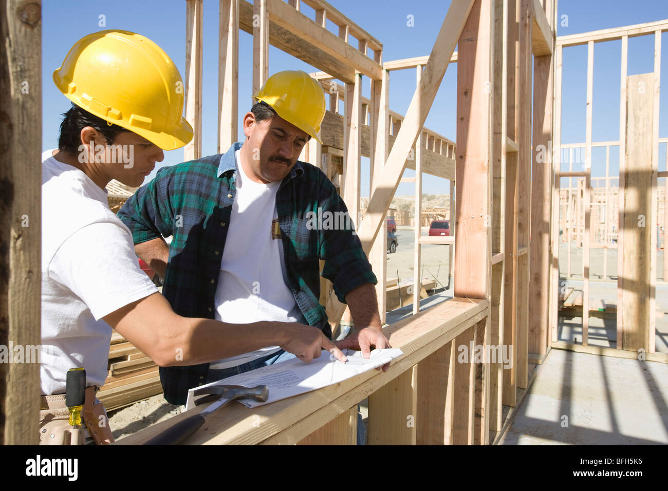 Construction workers reading blueprint on building site stock photo construction workers reading blueprint on building site malvernweather Images