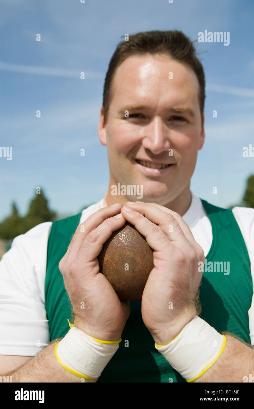 Male shot putter gripping shot, portrait - Stock Image
