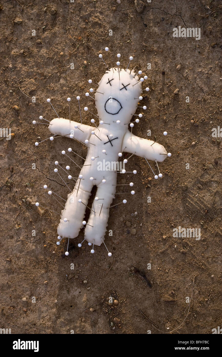 A simple voodoo doll lying on the ground in the dirt Stock