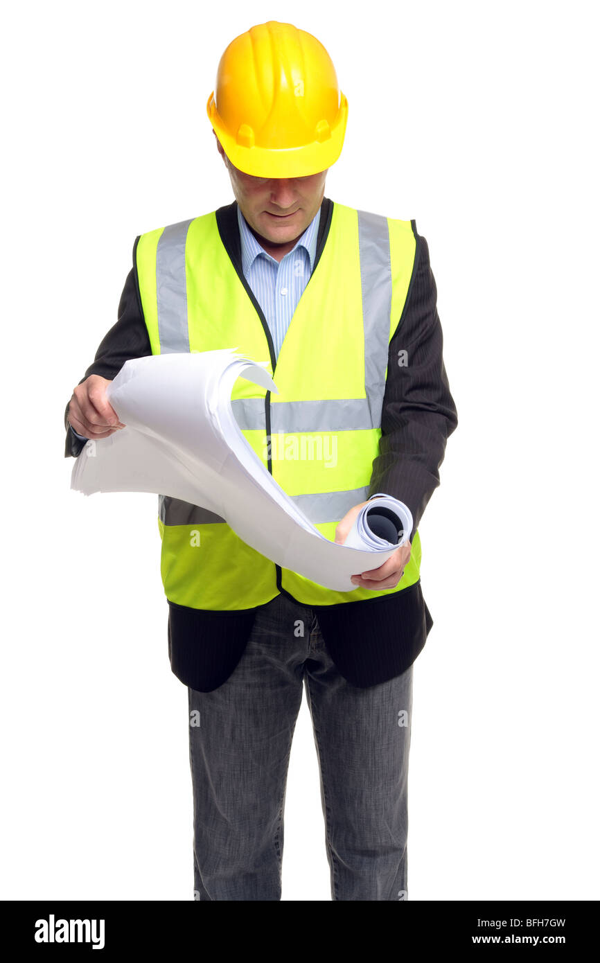 Building contractor wearing safety clothing as he unfolds some blueprints, isolated on a white background. - Stock Image