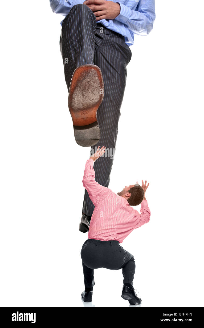 A businessman about to be stepped on by a giant foot, isolated on a white background. - Stock Image