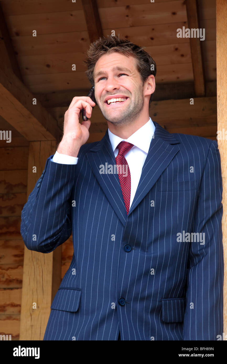 Businessman in his late twenties standing at a rural bus stop talking on his mobile phone - Stock Image