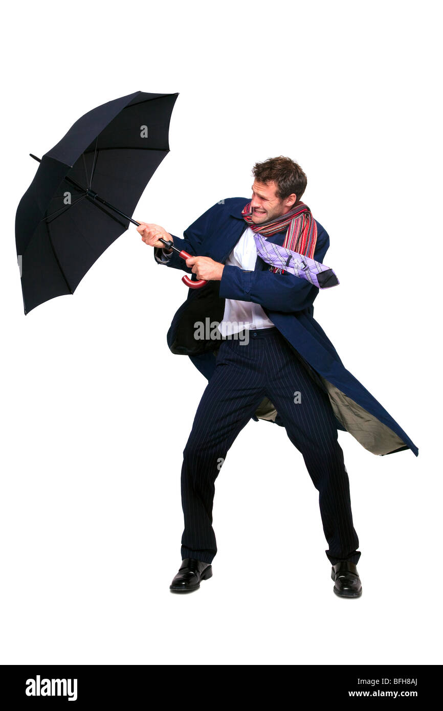 Studio shot of a businessman struggling with an umbrella in the wind, isolated on a white background. - Stock Image