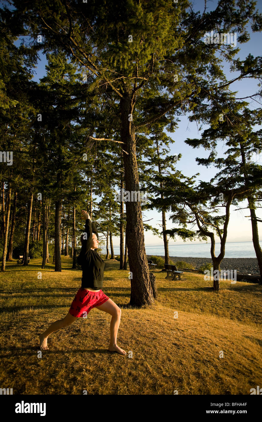 A womanduring a yoga pose at Kitty Coleman Beach campground.  Courtenay Comox Valley Vancouver Island British Columbia Stock Photo