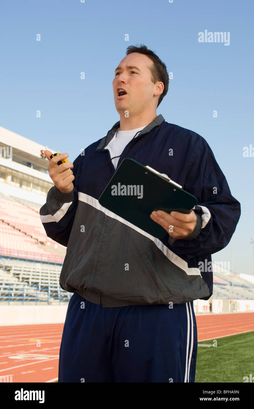 Sports coach looking at stopwatch - Stock Image