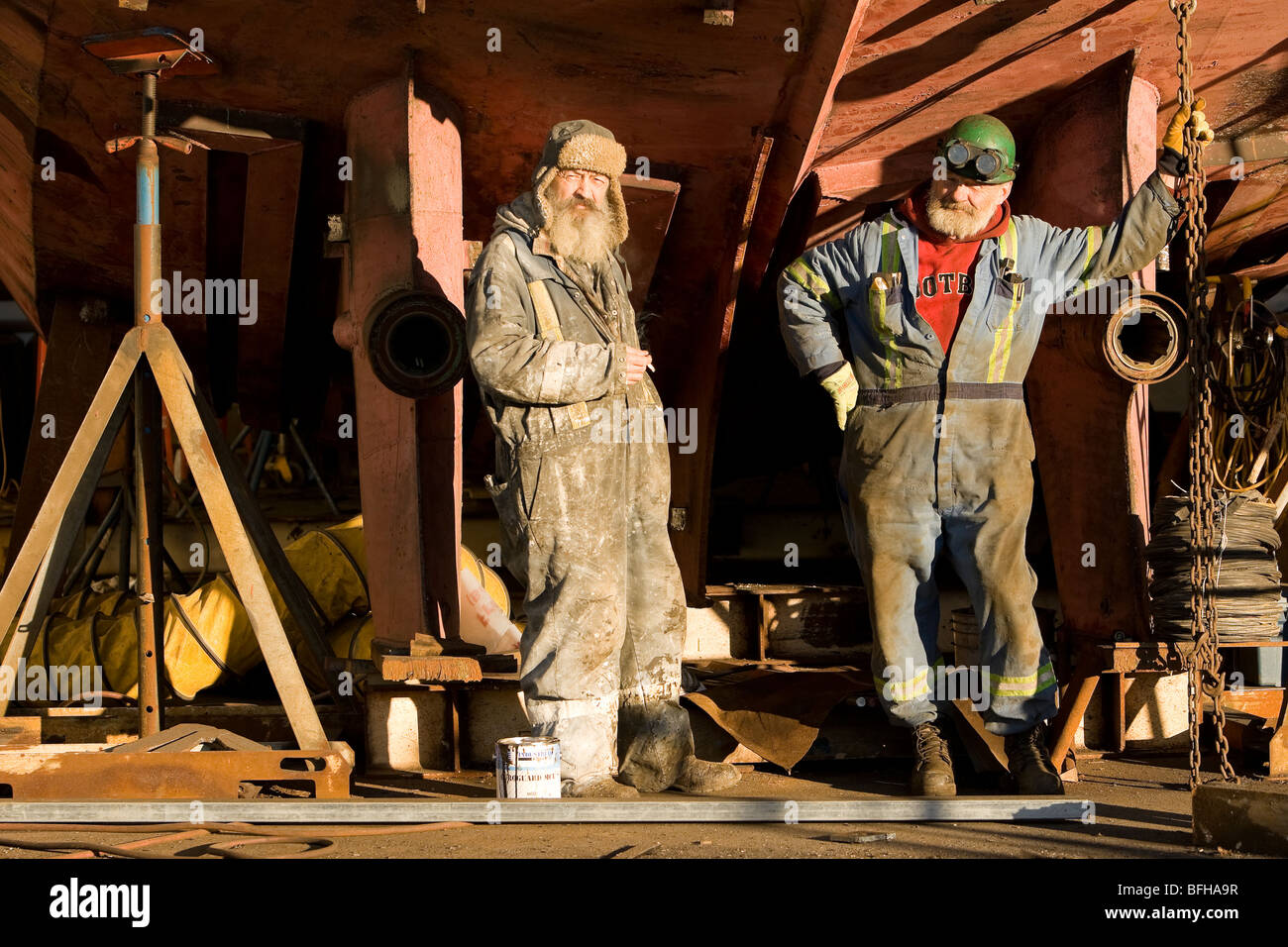 Welder and ship-painter relax during a break while refitting a tugboat at a shipyard in Campbell River.  Vancouver - Stock Image