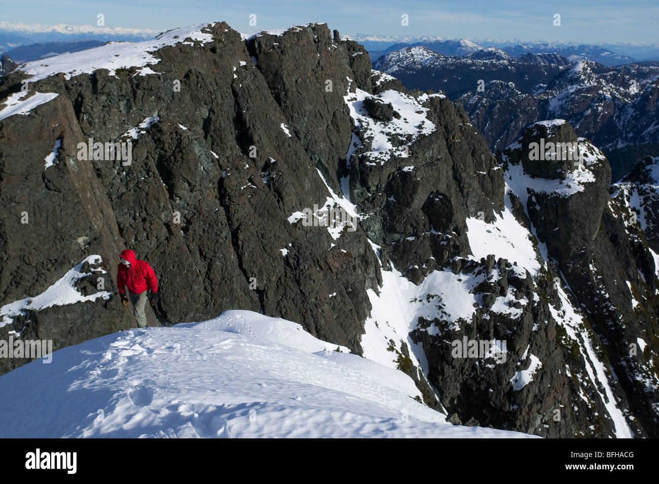 Lone climber ascends to summit snowfield of Mt. Cain looking South towards Campbell River on central Vancouver Island. - Stock Image