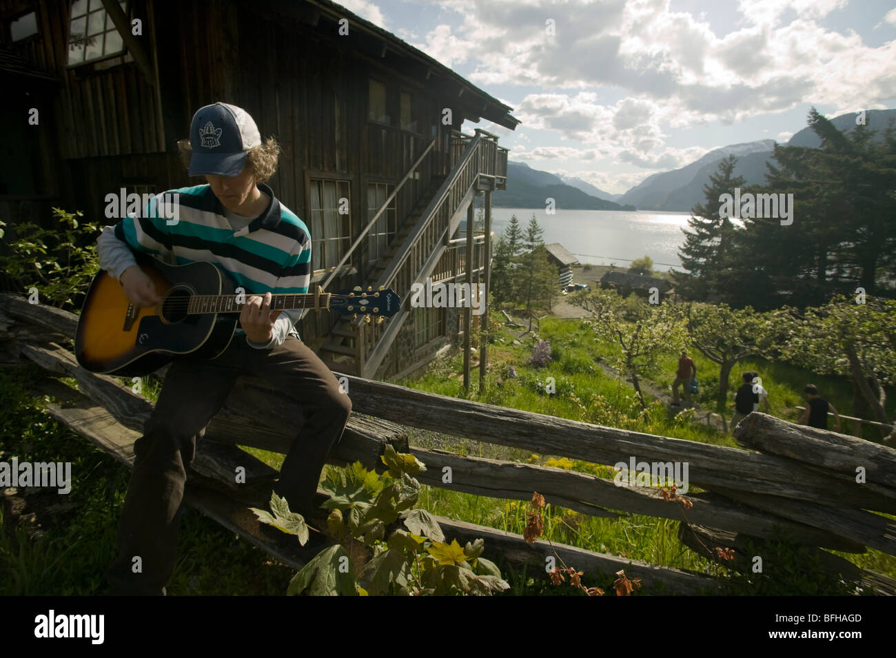 A young man plays his guitar  at the well known Strathcona Park Lodge, British Columbia, Canada. - Stock Image