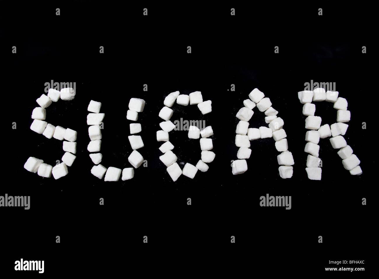 Sugar written in sugar lumps on a black studio background. - Stock Image