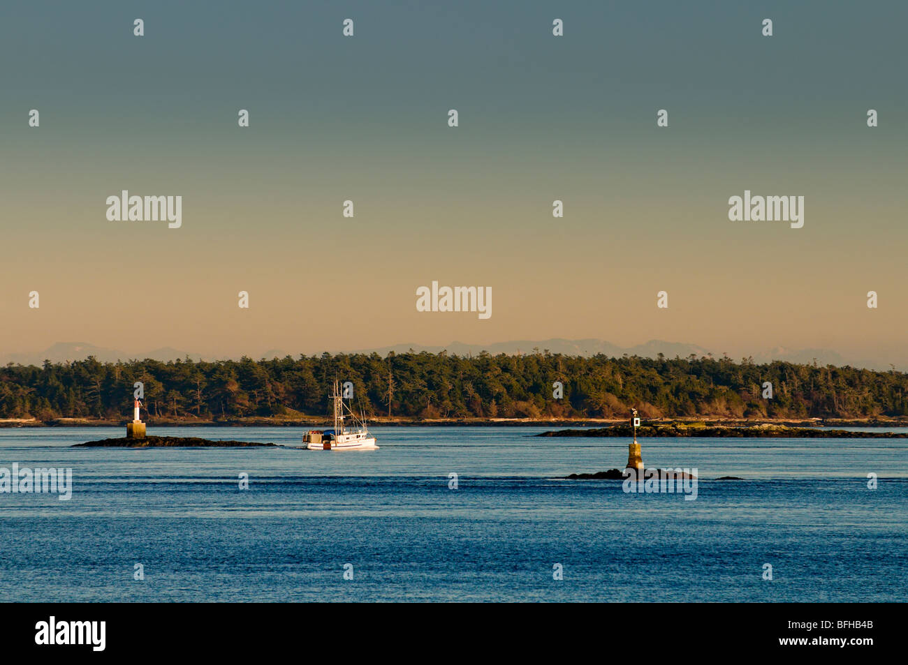 A fishing boat motors along between navigation markers off Oak Bay, Victoria BC. - Stock Image