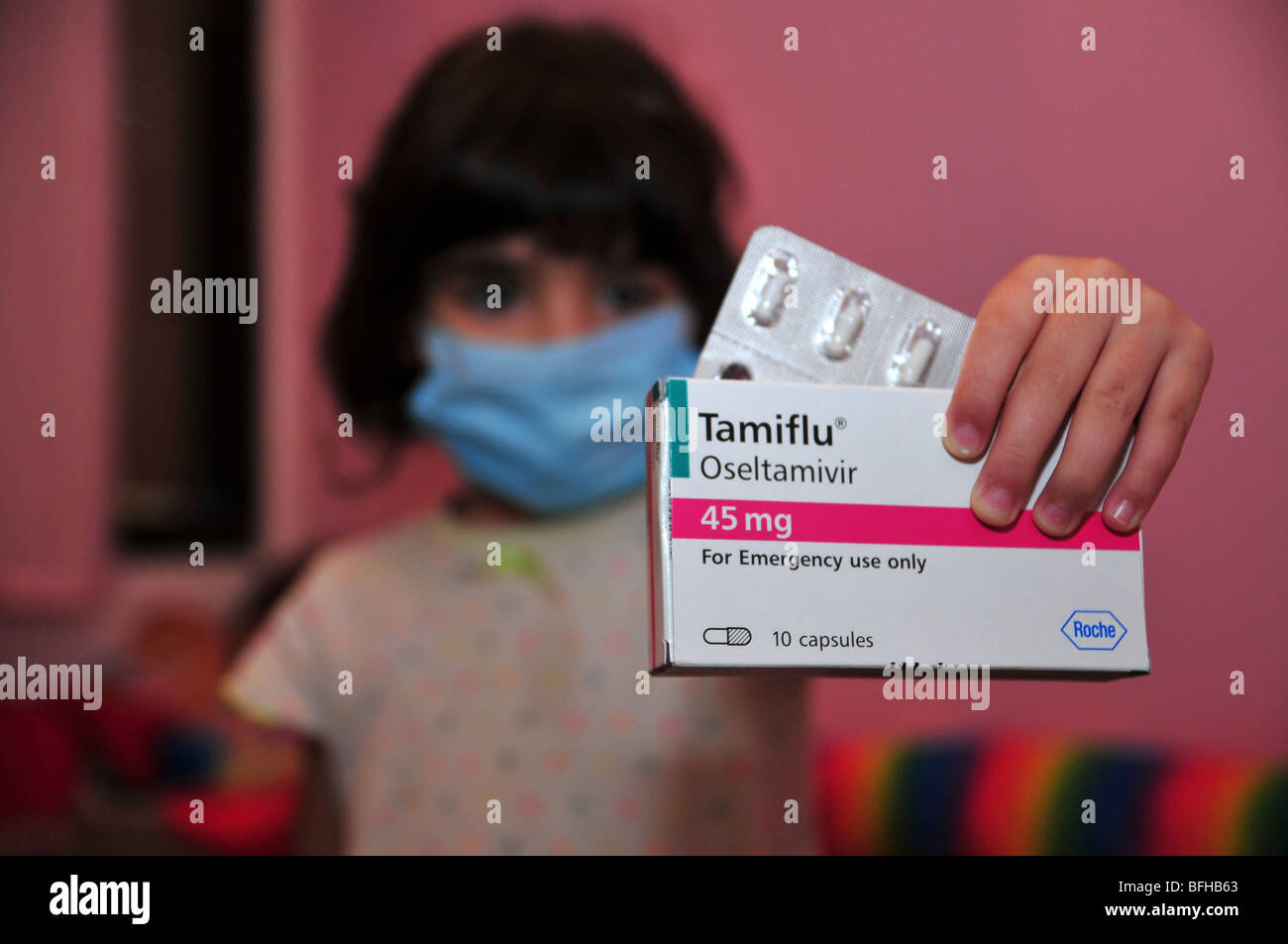 A young girl wears a medical face mask and holds a pack of Tamiflu tablets agaist Swine flu, October 30, 2009. - Stock Image