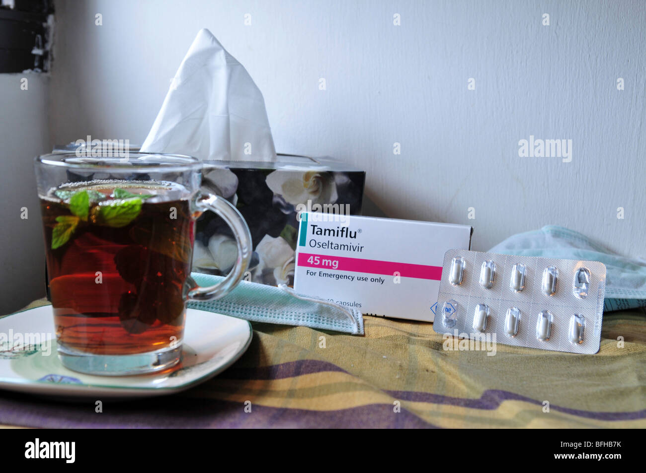 A medical face mask, a pack of Tamiflu tablets, tissues and a cup of hot mint tea agaist Swine flu, October 30, - Stock Image