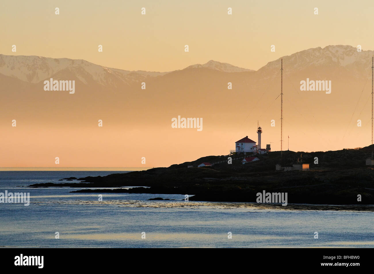 The Olympic Mountains provide a dramatic backdrop for Trial Island Light  near Victoria BC. - Stock Image