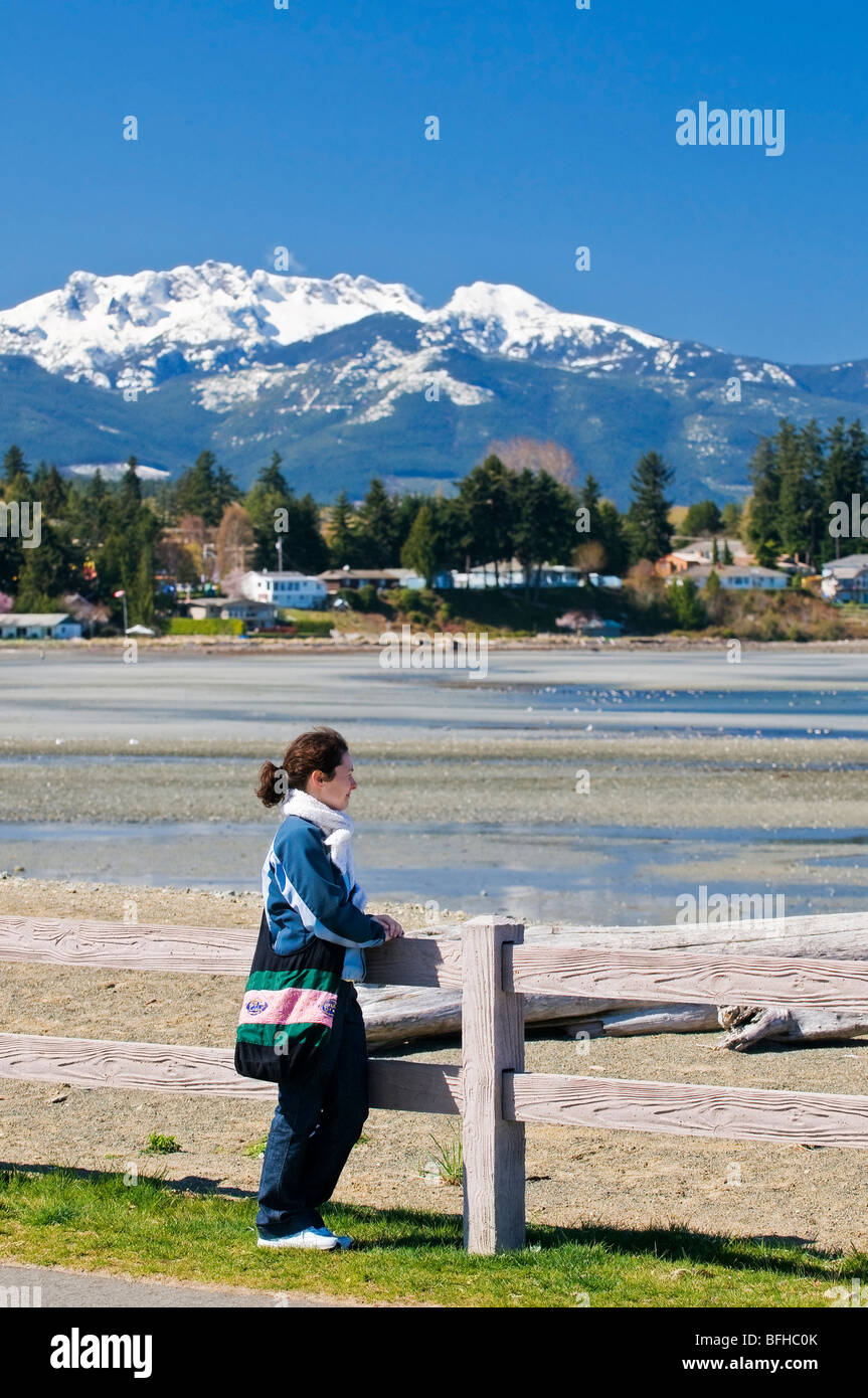 Snow-capped Mount Arrowsmith looms over the beach at Parksville BC. - Stock Image