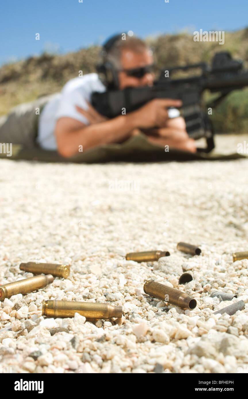 Man aiming machine gun at firing range, focus on bullets in foreground - Stock Image