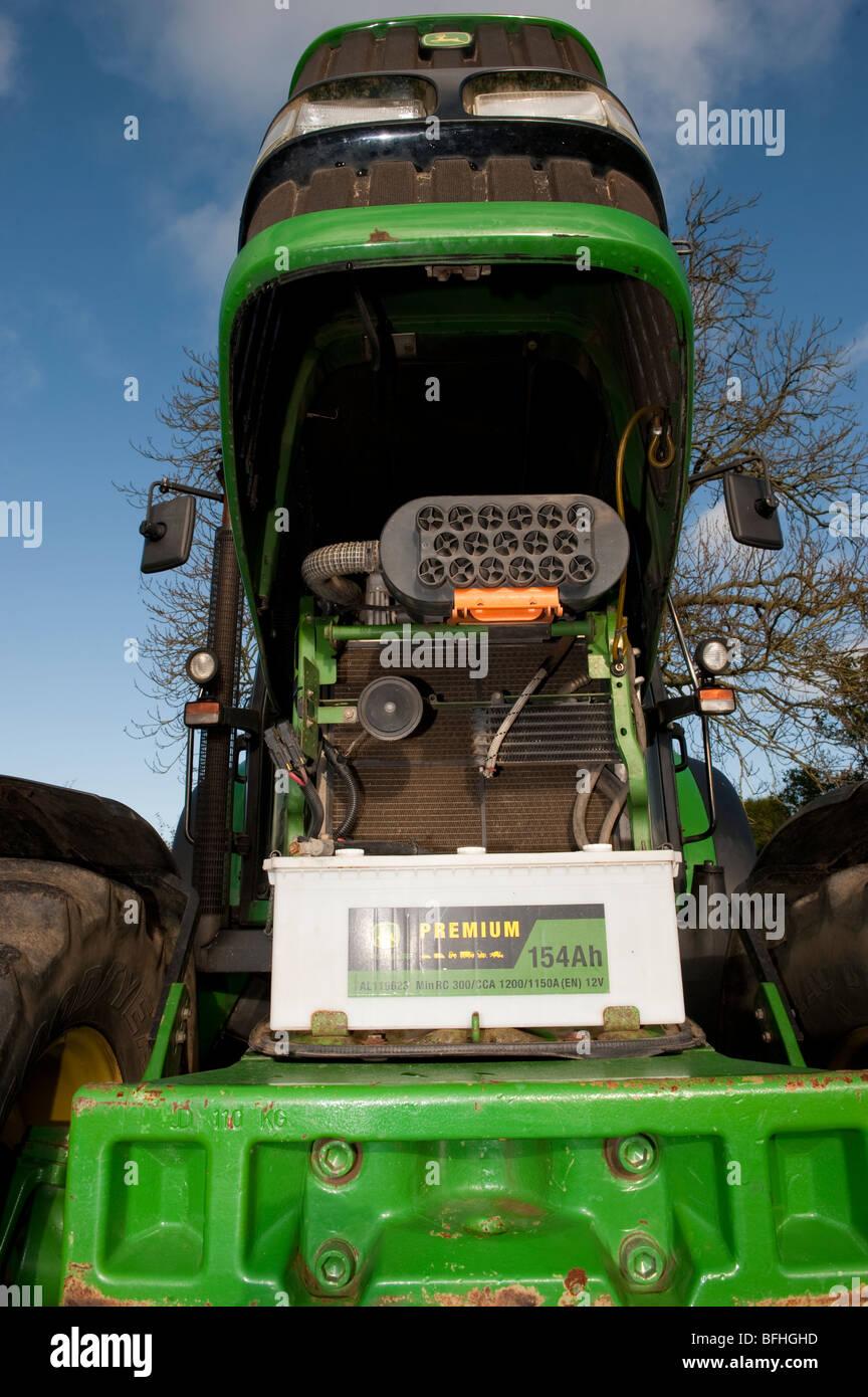 John Deere tractor with bonnet up in field. - Stock Image