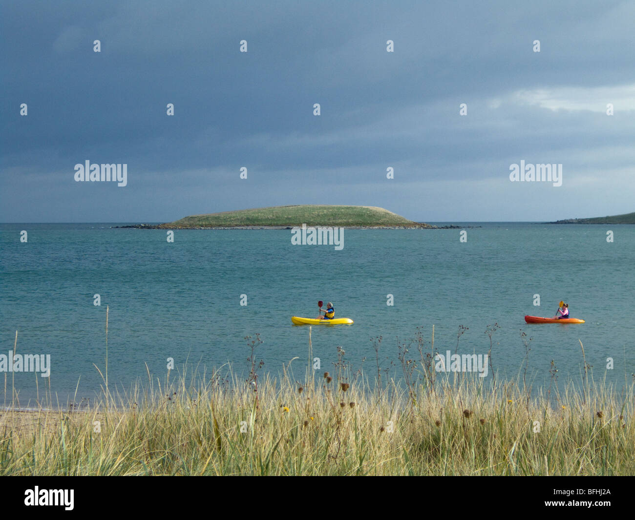 A pair of canoeists enjoying a still day in the waters of Skerries beach, north county Dublin, Ireland - Stock Image