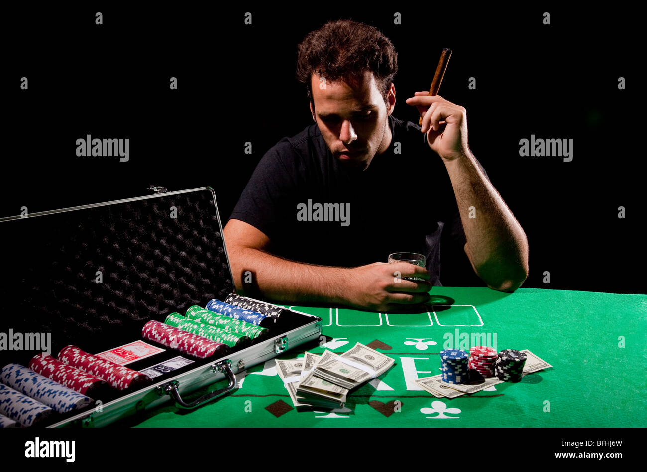 A young male gambler at the gambling table holding a cigar model release available - Stock Image
