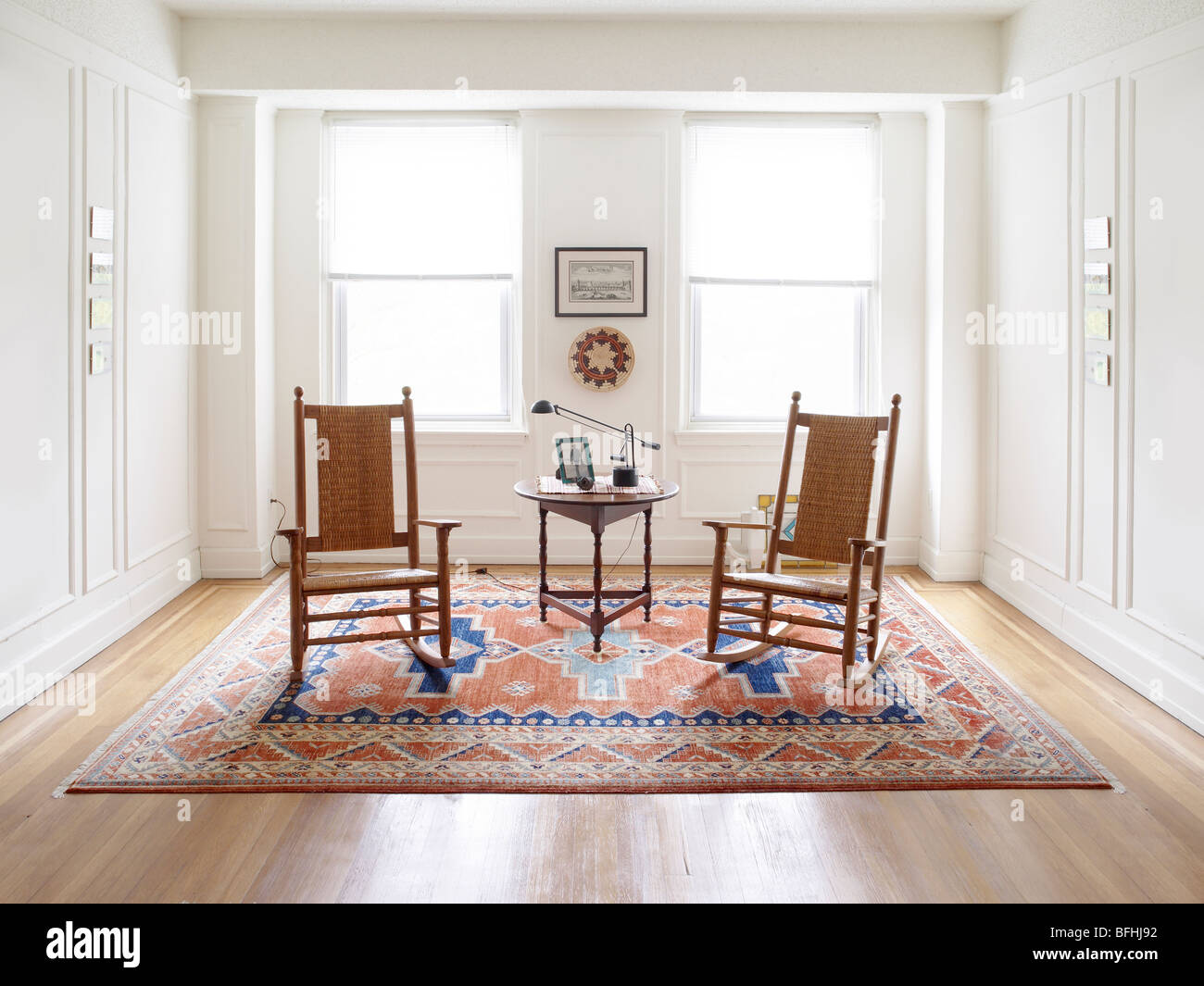 Two Rocking Chairs in White Room With Bright Light Through Windows - Stock Photo