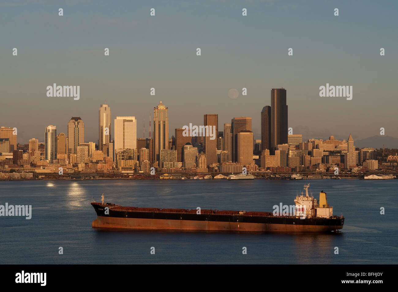 Seattle skyline from West Seattle with tankers in Elliott Bay at sunset with moonrise  Washington State USA Stock Photo