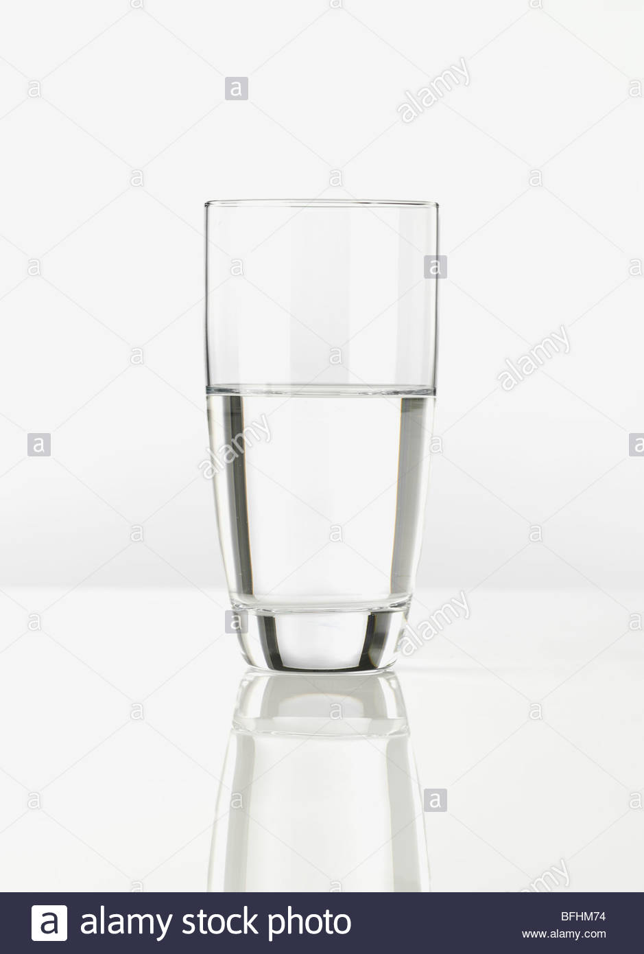 a glass of still spring water half full or half empty  photographed on white - Stock Image