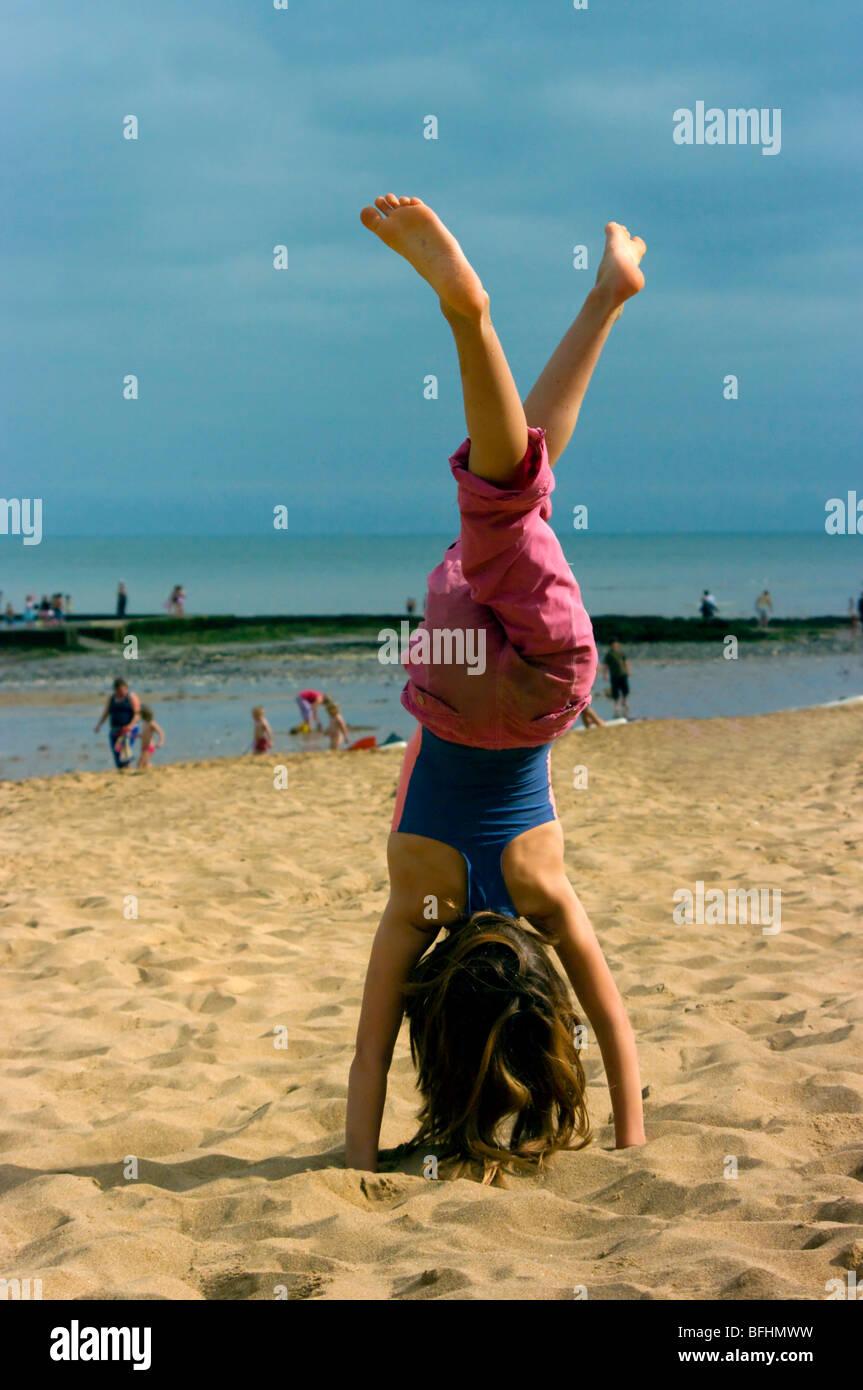 uk england seaside kent broadstairs girl child handstand on beach - Stock Image