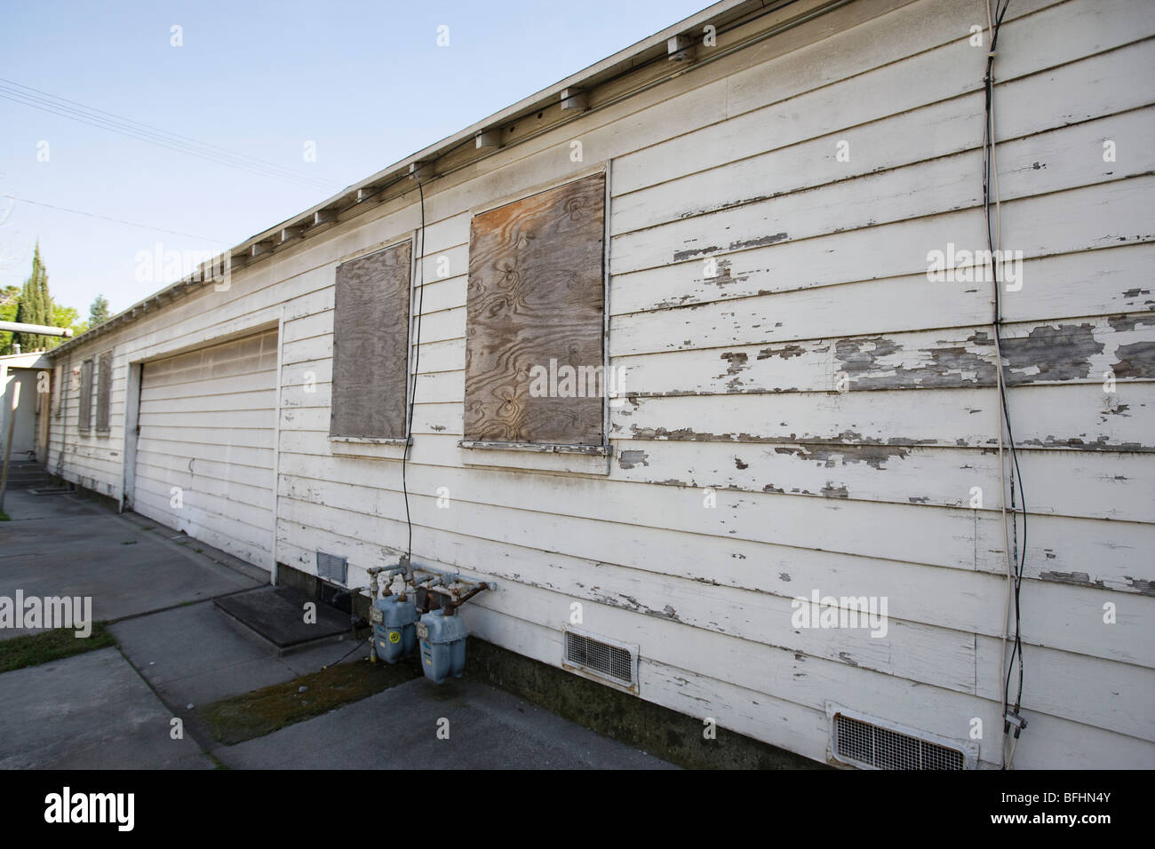 Abandoned Building With Boarded Windows and Peeling Paint - Stock Image