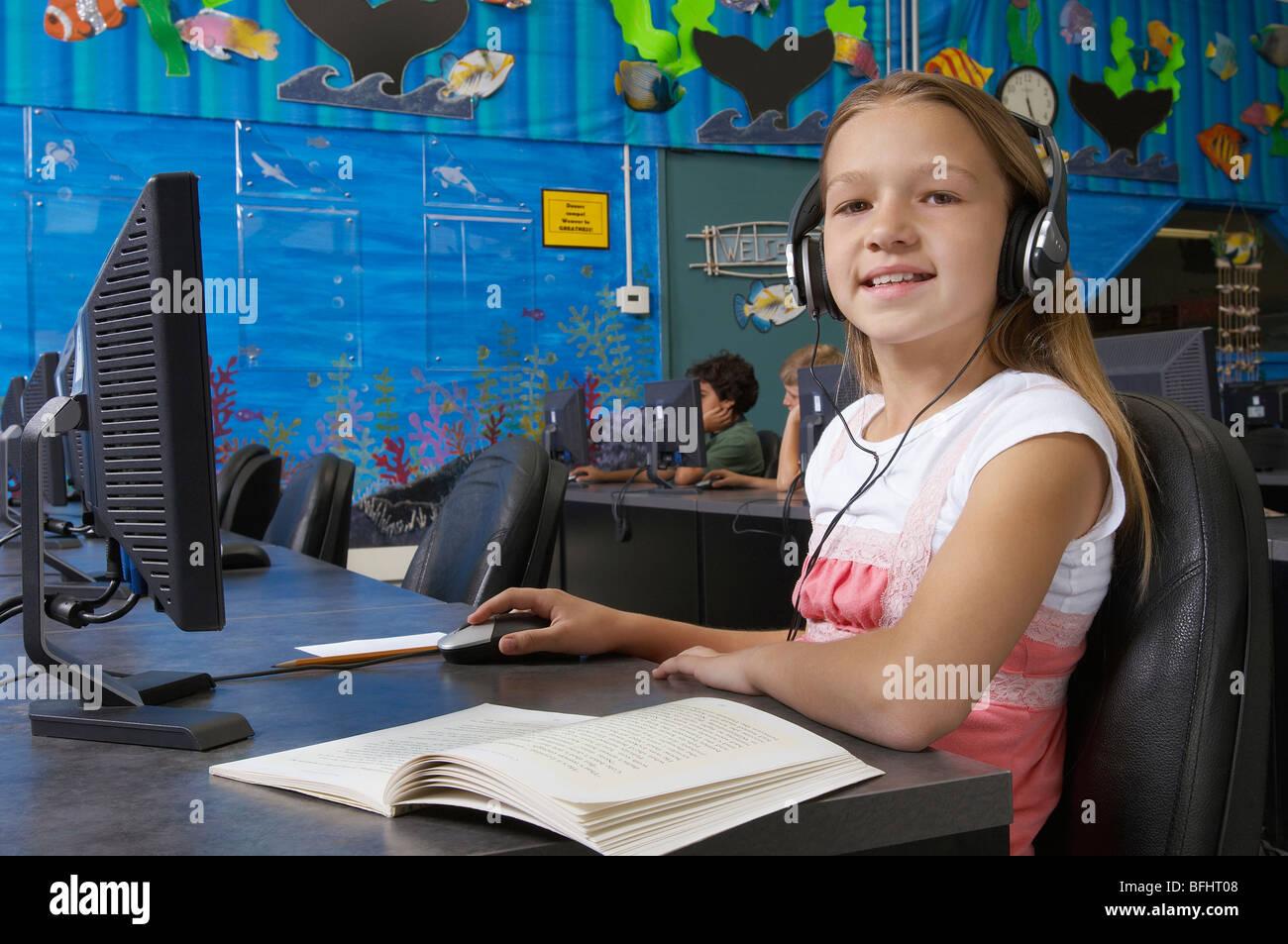 School girl wearing headphones in computer room, portrait Stock Photo