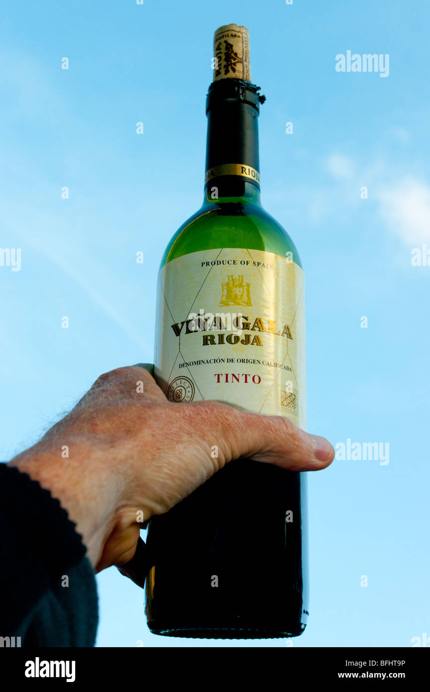 wine bottle rioja held aloft - Stock Image