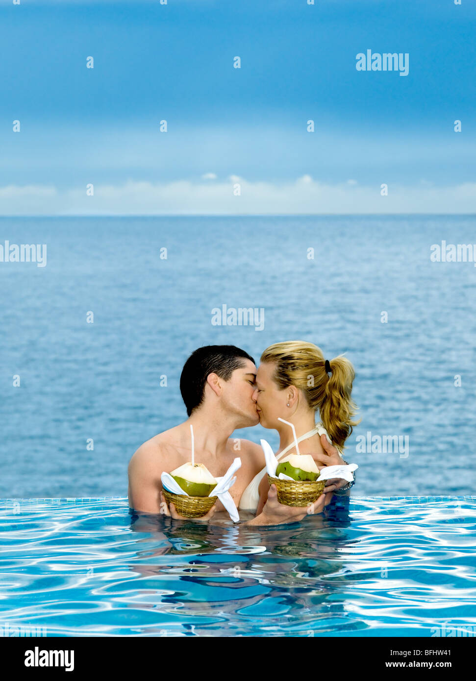 beautiful caucasian couple enjoying their vacation in a beautiful swimming pool by the seaside - Stock Image