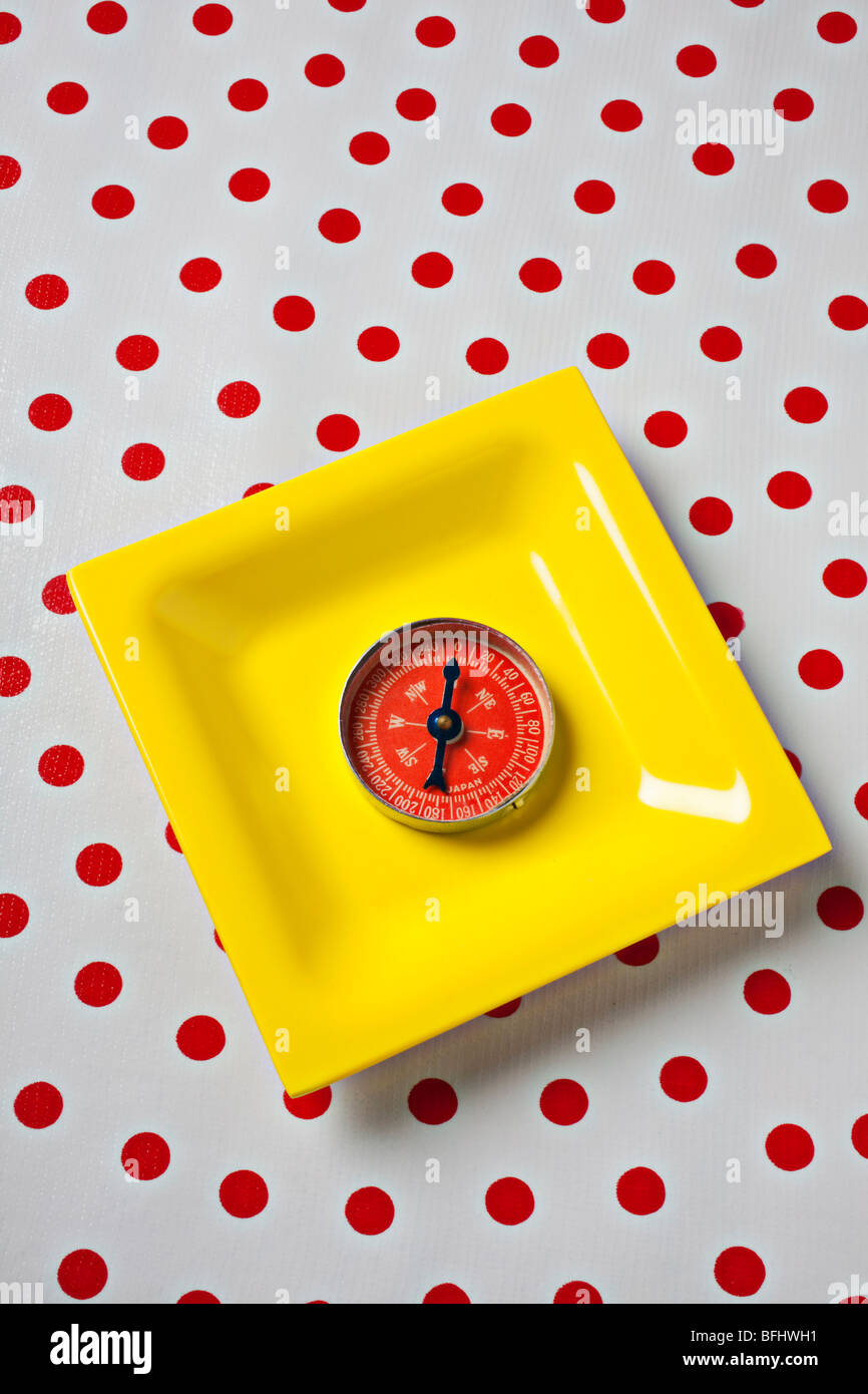 Red compass on yellow plate - Stock Image