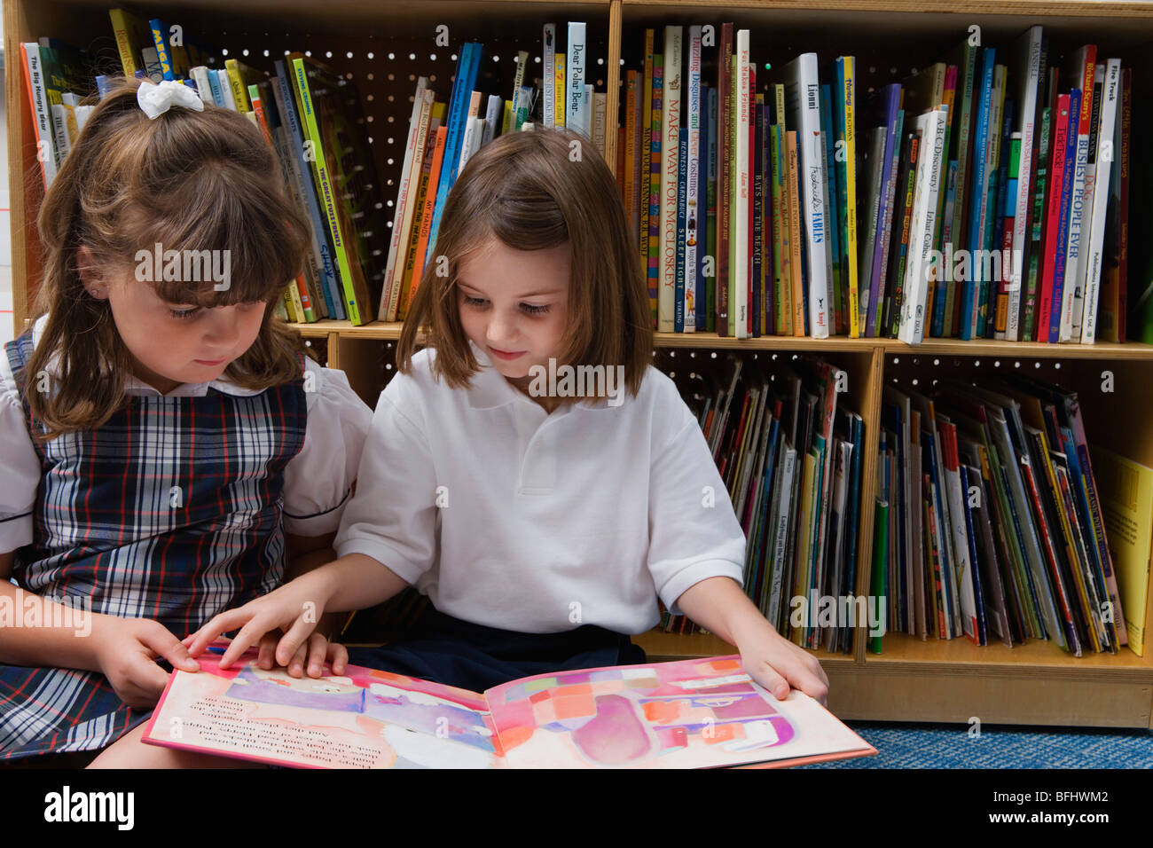 Little Girls Looking at a Picture Book - Stock Image