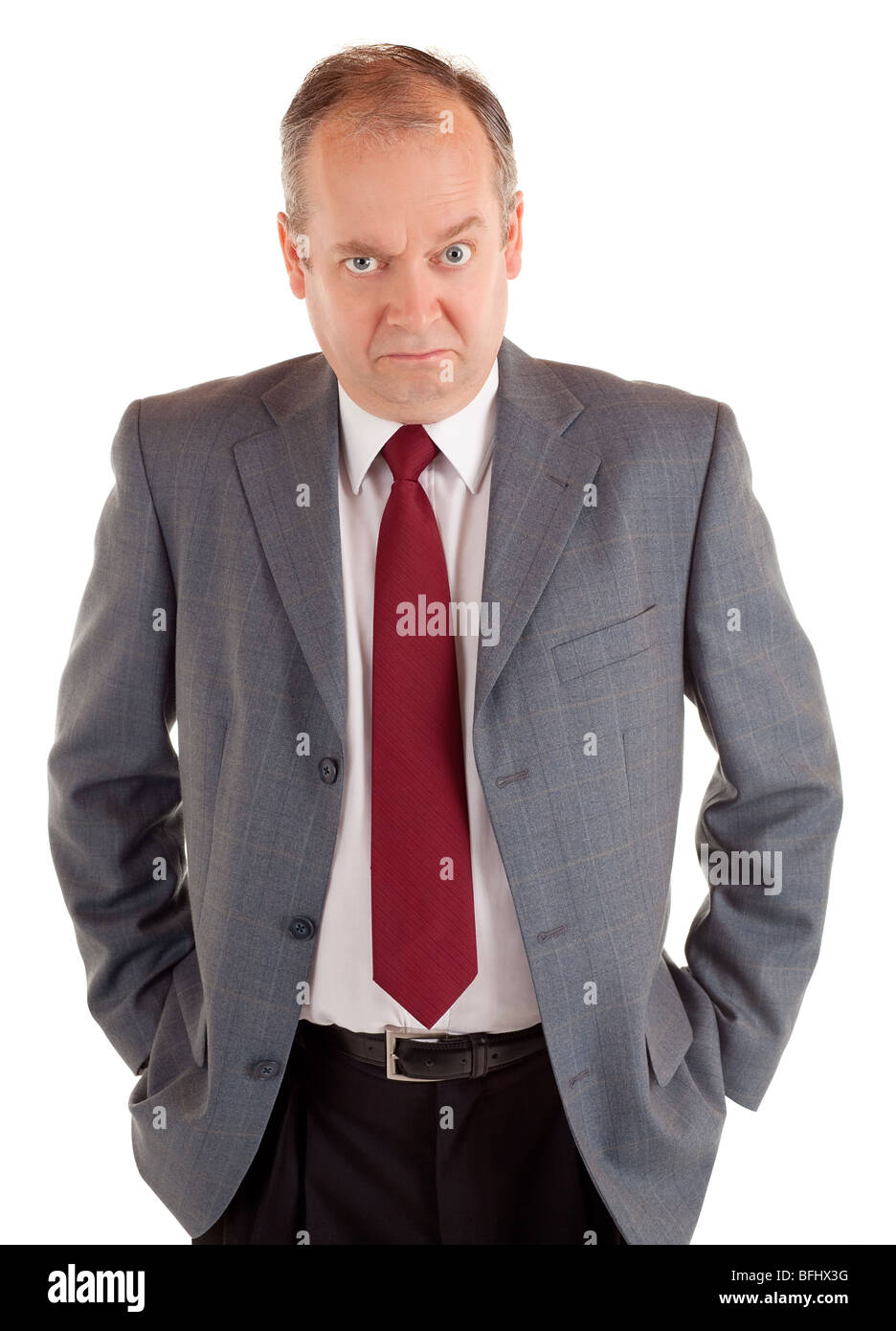 A businessman is standing and seriously looking at the camera with a scowling expression. - Stock Image