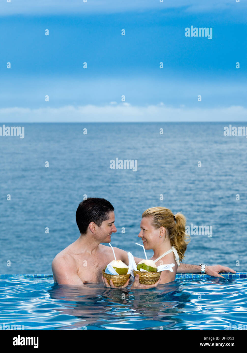 beautiful caucasian couple enjoying their vacation in a swimming pool by the seaside drinking coconut milk - Stock Image