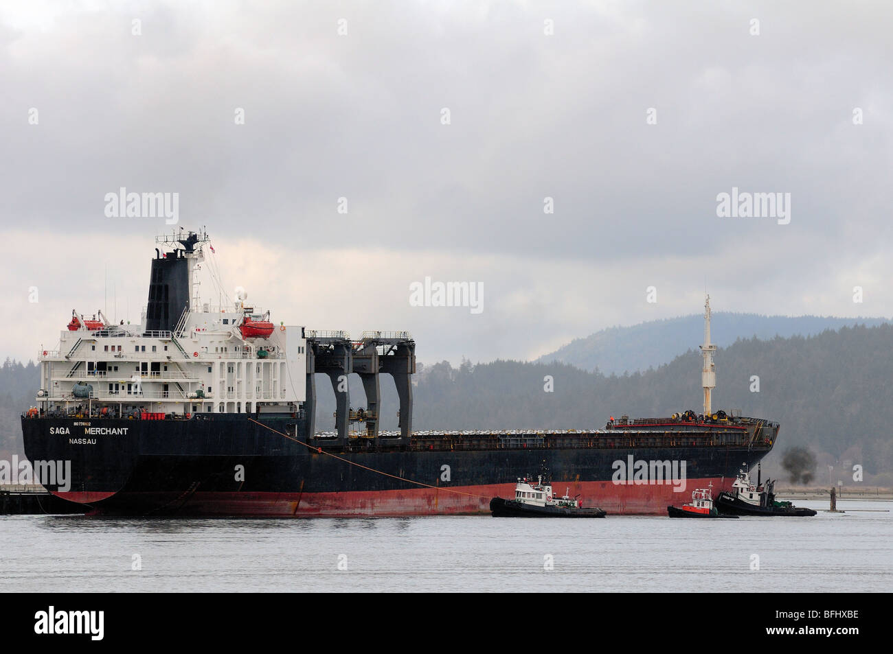 Tugs assist freighter into dock in Cowichan Bay, BC. - Stock Image