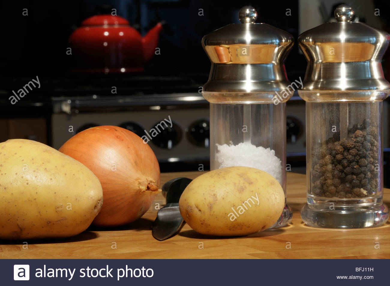 Potatoes and onion along with salt and pepper mills on a chopping board, Dorset, England, UK - Stock Image