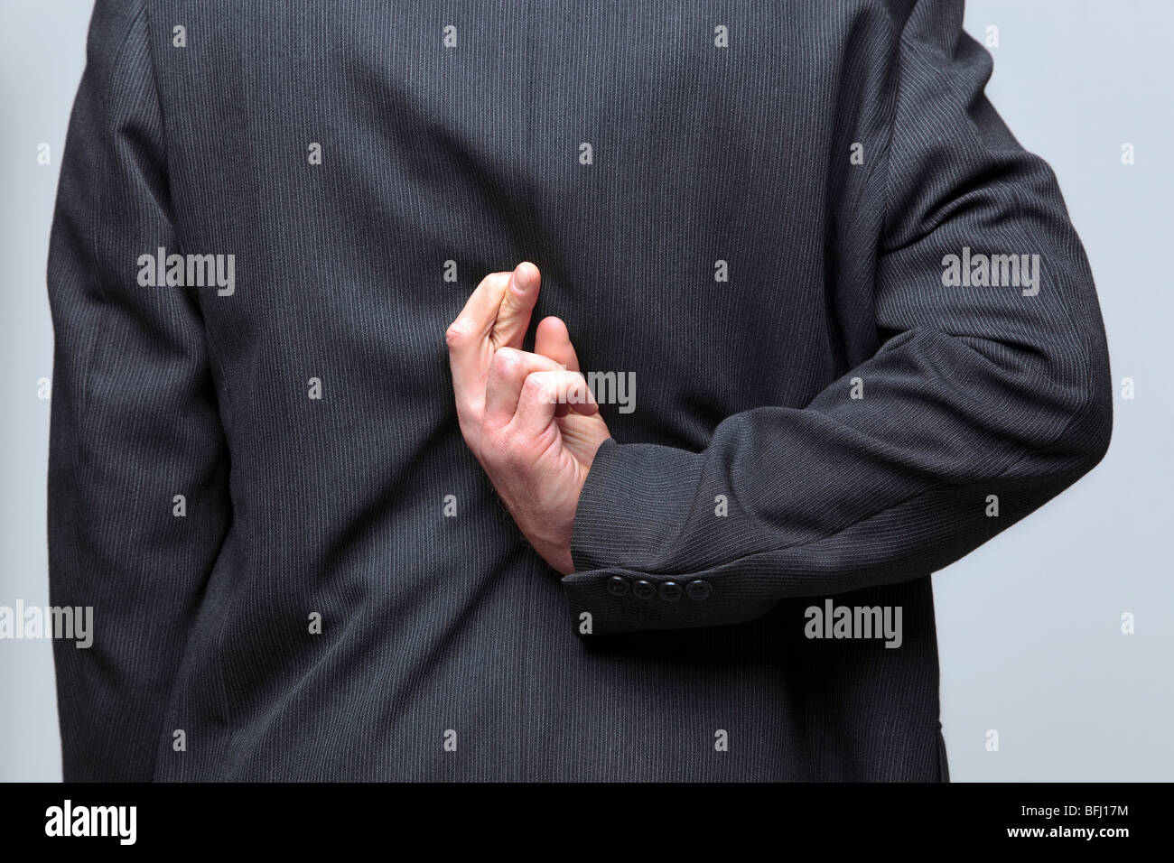 Businessman with his fingers crossed behind his back - Stock Image