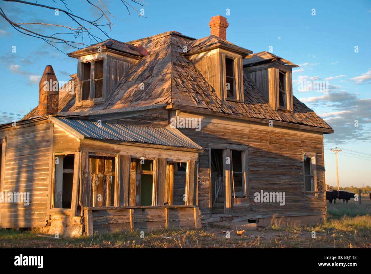 An old deserted house at sunset makes the perfect backdrop for Halloween. - Stock Image